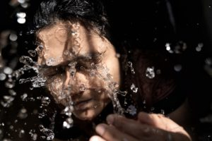 woman in black shirt with water droplets